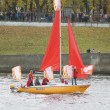One of the sailboats with red sails on the Olympic torch relay — Stok fotoğraf