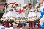 Girls in traditional costumes dancing on stage — Stock Photo
