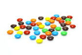 Lots of colorful candies spread on white background — Stock Photo