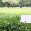 White signboard on grass field — Stock Photo
