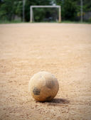 An old soccer ball on ground, goal is the background — Stock Photo