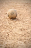 Old soccer ball on earth playground — Stockfoto