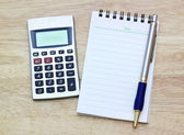 Notebook, silver ballpen and calculator on wooden desk — Stock Photo