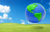 Clay earth over the green grass field eco concept — Stock Photo