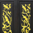 Flower carved gold paint on wood door — Stock Photo