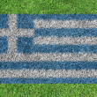 Flag Greece as a painting on green grass — Stock Photo