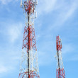 Cell phone and communication towers against blue sky with scatte — Stock Photo
