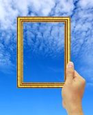 Hand hold a gold photo frame — Stock Photo