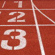 Running track numbers one two three in stadium — Stock Photo #13442860