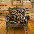 Foto Stock: Antique armchair in brick wall room with frame hanging on.