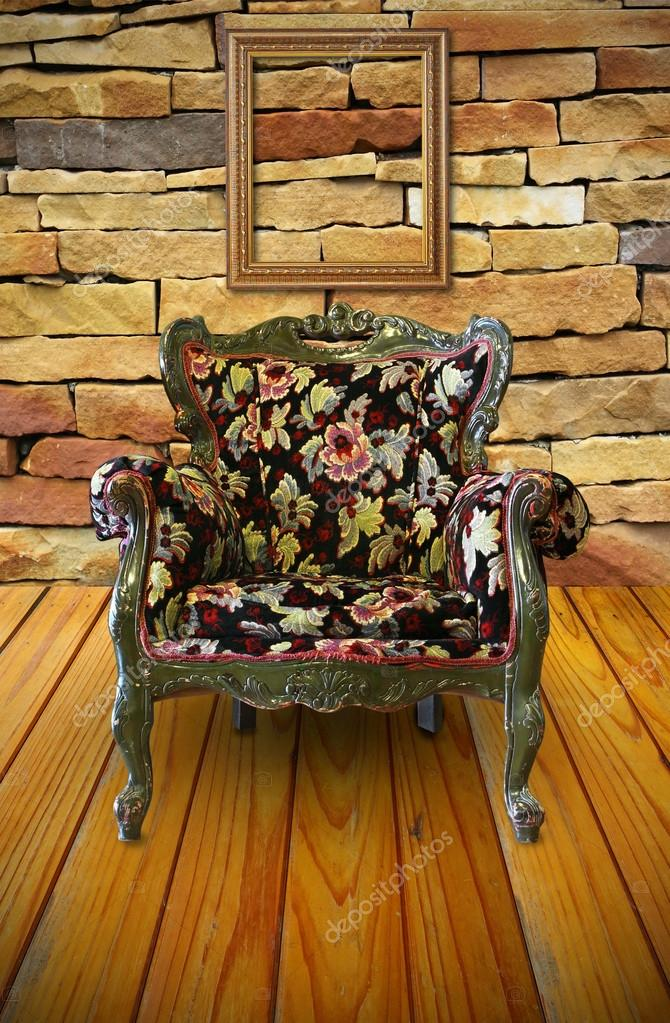 Antique armchair in the brick wall room with a frame hanging on ...