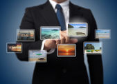 Business man pushing virtual screen with different images of tro — Stock fotografie