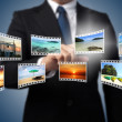 Businessman pushing many image in film button on the whiteboard. — Stock Photo #13578304