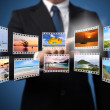 Businessman pushing many image in film button on the whiteboard. — Stock Photo #13578310