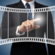 Business man touching on film strip icon — Stock Photo