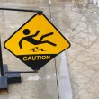 Yellow sign alerts for wet floor. - Stock Photo