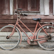 Old bicycle leaning against grungy barn — Stock Photo #14032393