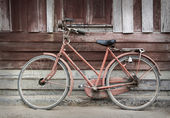 Old bicycle leaning against grungy barn — Stock Photo