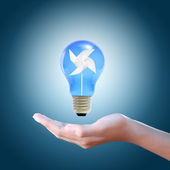 Paper windmill in a blue light bulb on women hand — Stock Photo