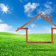 Photo: Wooden house icon concept on green grass field landscape