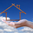 Wood  house in hand on blue sky - Stock Photo