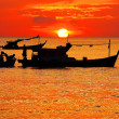 Silhouette of fishermen with yellow and orange sun in the backgr — Stock Photo