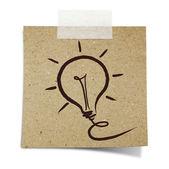 Main dessiner ampoule sur papier recycle scotchée — Photo
