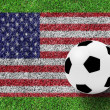 Soccer ball on flag of American as painting on green grass backg — Stock Photo
