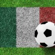 Soccer ball on flag of italy as painting on green grass backgrou — Stock Photo