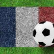 Soccer ball on flag of france  as painting on green grass backgr — Stock Photo