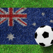 Soccer ball on Australia flag as a painting on green grass — Stock Photo