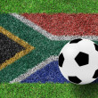 Soccer ball on flag of south africa as a painting on green grass — Stock Photo