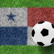 Soccer ball on flag of Panama as a painting on green grass - Stock Photo