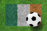 Soccer ball on Flag Republic of Ireland as a painting on green g — Stock Photo