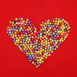 Colorful beads heart shape isolated on red background  — Stock Photo