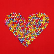 Colorful beads heart shape isolated on red background — Stock Photo #37055193
