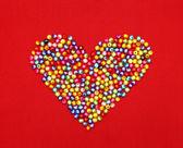 Kleurrijke kralen hart vorm geïsoleerd op rode achtergrond — Stockfoto