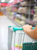 Woman hand with shopping cart in supermarket — Stock Photo