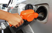 Woman hand refilling gas to car with fuel on a filling station. — Stock Photo