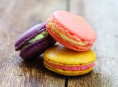 Colorful french macaroons stacked on wood table. — Photo