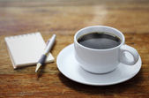Coffee cup notebook and pen on the wooden table background  — Stock Photo