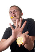 Young man tasting lemon. thats sour — Stock Photo