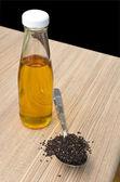 şişe ve tahta kaşık, siyah susam, susam yağı — Stok fotoğraf