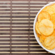 Potato chips in white bowl on bamboo mat — стоковое фото #33153965