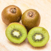Whole kiwi fruit and his sliced segments isolated — Photo