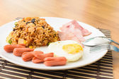 American fried rice with pork sausage, bacon and fried egg — Stock Photo