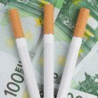 Cigarettes lying on the bills — Stock Photo