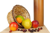 Fruit spill out of the basket on a bed of straw — Stock Photo