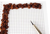 Pen and notepad with coffee beans — Stock Photo