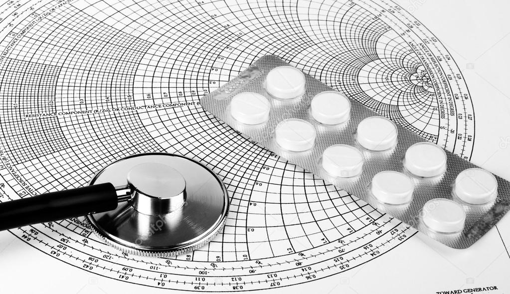 Stethoscope and pills on the sheet with a diagram  Stock Photo #12699613